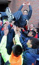 ジュニア育成が結実して、10年ぶりの総合優勝を果たした大村・東彼。選手たちに胴上げされる野口総監督(九州電通)=長崎市茂里町、長崎新聞社前