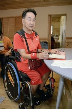 ほっとはうすで名刺作りの仕事に取り組む胎児性水俣病患者の松永幸一郎さん=水俣市