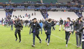 サッカーのフランス対ドイツ代表の親善試合が行われていた競技場近くで爆発が起き、ピッチに避難する観客=2015年11月13日、パリ郊外サンドニ市(ゲッティ=共同)