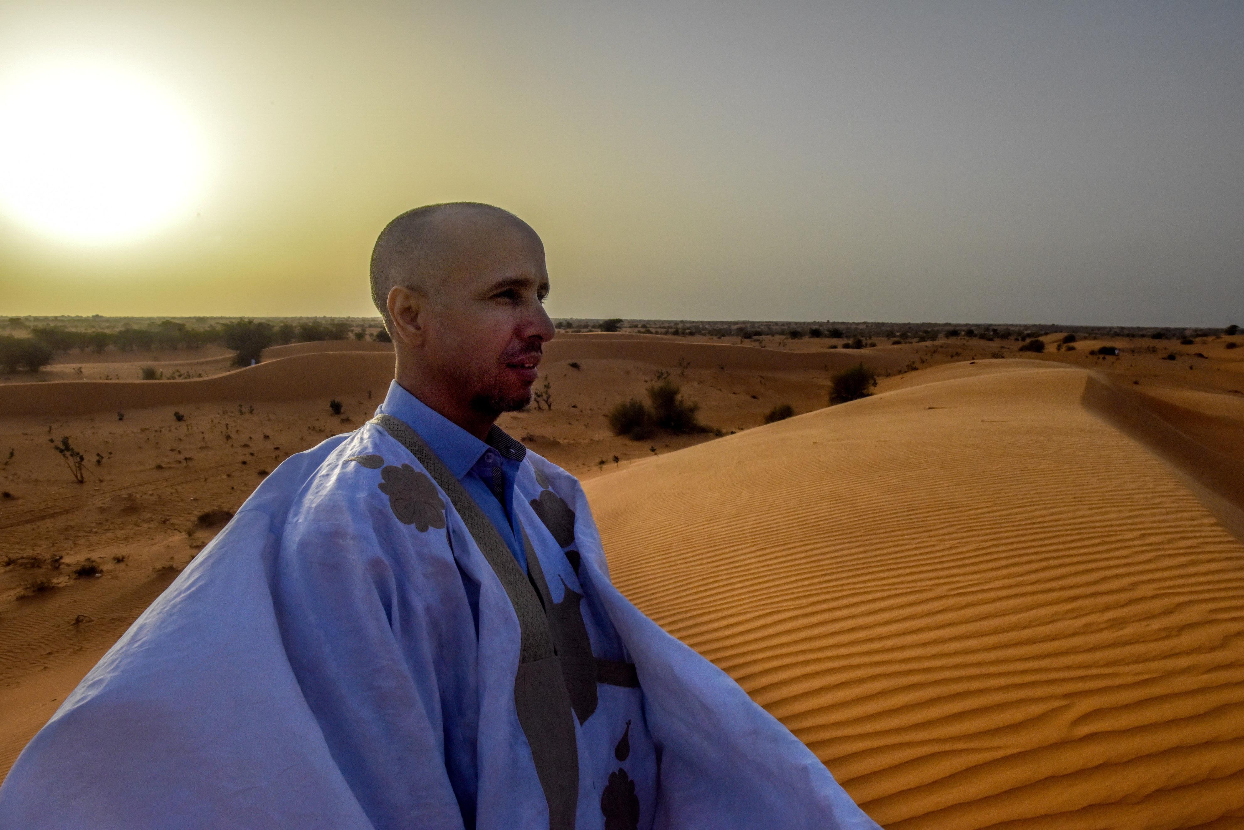 モーリタニアの首都ヌアクショット郊外の砂丘で、夕日を背にたたずむモハメドゥ・スラヒ。砂漠に座り、思いにふける平和な時間が好きだという(撮影・中野智明、共同)