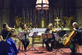 16日、ウィーンのミノリテン教会で、東日本大震災の津波のがれき木材で作った弦楽器を弾く演奏家ら(共同)