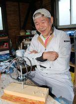発明した器具を前に「みなさんに使ってもらえてうれしい」と話す岳野さん