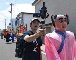 天妃様行列を撮影する佐藤さん(中央)