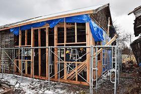 倒壊回避のため破損した柱の入れ替えや屋根の補修が行われている「九号兵舎」=12日午後1時半ごろ、鯵ケ沢町北浮田町
