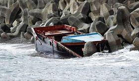 消波ブロックに漂着した木造船=20日、深浦町広戸