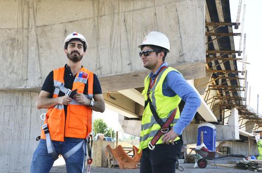 サンティアゴ郊外の高架橋建設現場で現場監督(右)と話すビクトル・ディアス。公共事業省で橋の耐震検査を担当する=2018年12月