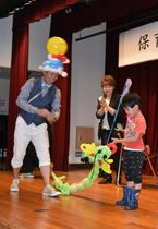 【園児と触れ合う東さん(中央)と小宮さん(左)=尾鷲市中村町の中央公民館で】
