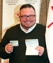 性別が「X」と記載された旅券と運転免 許を手に笑顔で写真に収まるジェマ・ヒッキーさん=2月13日、在日カナダ大 使館