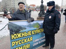 19日、モスクワ中心部のプーシキン広場で「南クリール諸島(北方領土)はロシアの土地だ」と書かれたプラカードを持つ男性(左)と警官(共同)