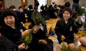 チューブに差し込んだ杉の葉を見せ合う児童