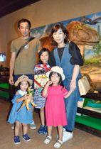 2万人目の来場者となった奥村翠月さん(中央)家族=鹿児島市の黎明館