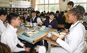 タンザニアの選手らと会話しながら給食を味わう生徒たち=長井市・長井南中