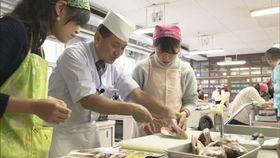 久保田和食料理長(右)の指導を受けながらタイの三枚おろしに挑戦する学生