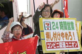 定時株主総会が開かれた東京都内のセブン&アイ・ホールディングスの本社前で抗議活動する人たち=23日午前