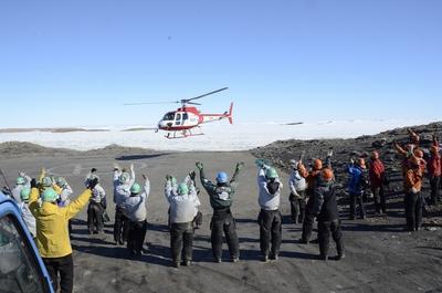 南極観測船しらせに戻るメンバーを見送る53次越冬隊員(オレンジのヘルメット)と54次隊員ら(緑のヘルメット)