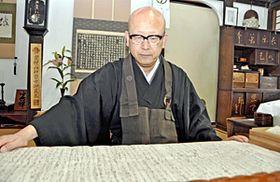 「150年の節目に慰霊したい」と語る中野住職。世良ゆかりの史料を見つめる=福島市舟場町・長楽寺