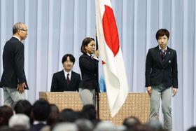 平昌冬季五輪の結団式で、団旗を手にする旗手代行の高梨沙羅。右は主将の小平奈緒=24日午後、東京都大田区