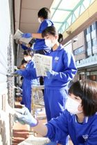 真剣な表情で空き店舗のシャッターにペンキを塗る生徒たち=五島市末広町