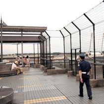 女性の遺体が見つかった現場の上部にある展望デッキを見回る常駐の警備員。写真奥側のフェンスの上部と下部のすきまをふさぐ措置も取られた=13日、成田空港第2ターミナル