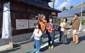 ボランティアガイド(左から2人目)の案内で映画「かぞくいろ」のロケ地巡りをする家族=昨年12月、阿久根市大川