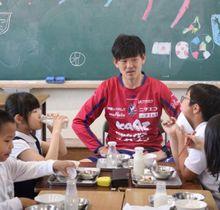 給食を食べながら上田選手(中央)と交流する児童たち=石井小