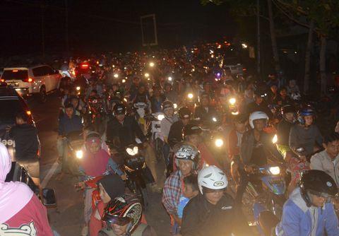 16日、インドネシア・ジャワ島中部で、津波を恐れて高台に避難しようとする人たち(AP=共同)