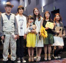 ドラマの完成を祝い、記念撮影する主人公の花咲ひまわりさん(右から3人目)ら=綾川町萱原、イオンシネマ綾川