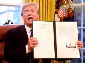 23日、ホワイトハウスで緊急輸入制限の発動を命じる文書に署名したトランプ米大統領(ゲッティ=共同)