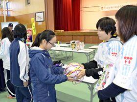 広野小児童らにサイン入りのサッカーボールを贈る元マリーゼ選手(右)=広野町中央体育館