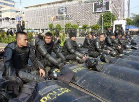 封鎖されたジャカルタ中心部の大通りを警備する警察の治安部隊=22日(共同)