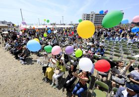 宮城県名取市閖上地区の「まちびらき」の式典で、風船を飛ばす市民ら=26日午前