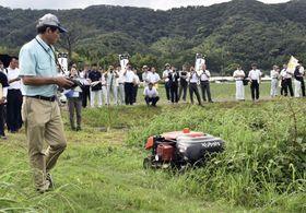 「スマート農業」の普及を目指すイベントで披露された、無線で操作できる草刈り機の実演=23日午後、鹿児島県志布志市