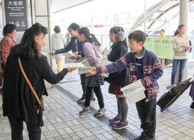 手作りの新聞を駅利用者に手渡す児童=湘南モノレール大船駅前