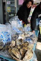 水揚げされたばかりの小長井牡蠣を買い求める客=諫早市、小長井町漁協直売店