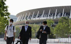 国立競技場を背に歩くマスク姿の人ら=4日午後、東京都新宿区