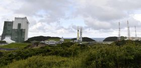 組立棟(左)から発射地点(右)に移動する、無人補給機「こうのとり」7号機を載せたH2Bロケット=14日午後、鹿児島県の種子島宇宙センター