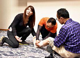 足首のねんざの対応について教える大城さん(左)