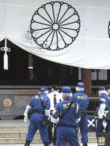 墨のようなものがかけられた拝殿につるされた幕の近くで調べる捜査員ら=19日午後、東京都千代田区の靖国神社