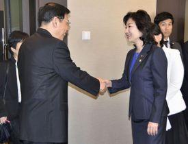 中国の苗ウ工業情報相(左)と握手する野田総務相=27日午後、東京都新宿区