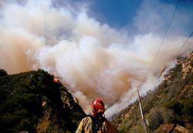 米西部カリフォルニア州マリブで消火を続ける消防隊員=11日(ロイター=共同)