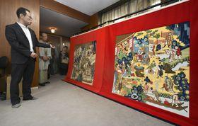 報道陣に公開された「木賊山」の正面を飾る前懸「金地唐人市場交流図」(右)=27日午後、京都市