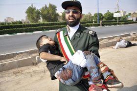 イラン南西部アフワズでの銃撃後、イラン革命防衛隊員に抱きかかえられる負傷した少年=22日(AP=共同)