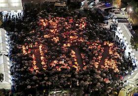 雨の中、「1・17」の文字を囲み、黙とうをささげる参加者ら=17日午前5時46分、神戸市中央区の東遊園地(撮影・三浦拓也)