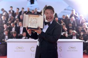 第71回カンヌ国際映画祭で最高賞パルムドールを受賞し、写真撮影に応じる是枝裕和監督=19日、フランス・カンヌ(ゲッティ=共同)