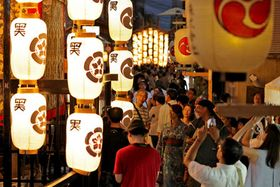駒形堤灯に照らされ、宵々山のそぞろ歩きを楽しむ人たち(22日午後7時29分、京都市中京区室町通三条下ル)