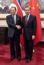 中国の王毅国務委員兼外相(右)と握手する北朝鮮の李容浩外相=7日、北京の釣魚台迎賓館(共同)