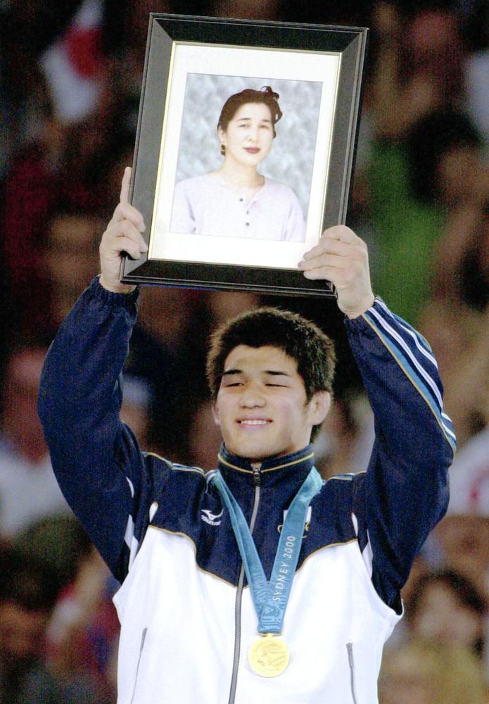2000年シドニー五輪柔道男子100㌔級の井上康生は表彰台で金メダルを胸に、母かず子さんの遺影を掲げた(共同)