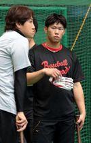 練習の合間にソフトバンクの内川(左)の話を聞く坂倉(撮影・井上貴博)
