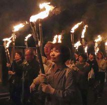 「稲むらの火祭り」でたいまつを手に練り歩く参加者=19日夕、和歌山県広川町