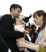 出身地の青森県野辺地町を訪れ、ファンの赤ちゃんを抱くサッカー日本代表の柴崎岳選手=13日午前